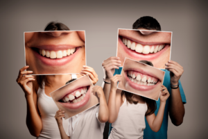 Family of four holding up photos of their teeth