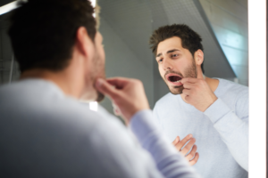 man looking at his tooth in mirror