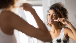 Woman Brushing Teeth in Mirror