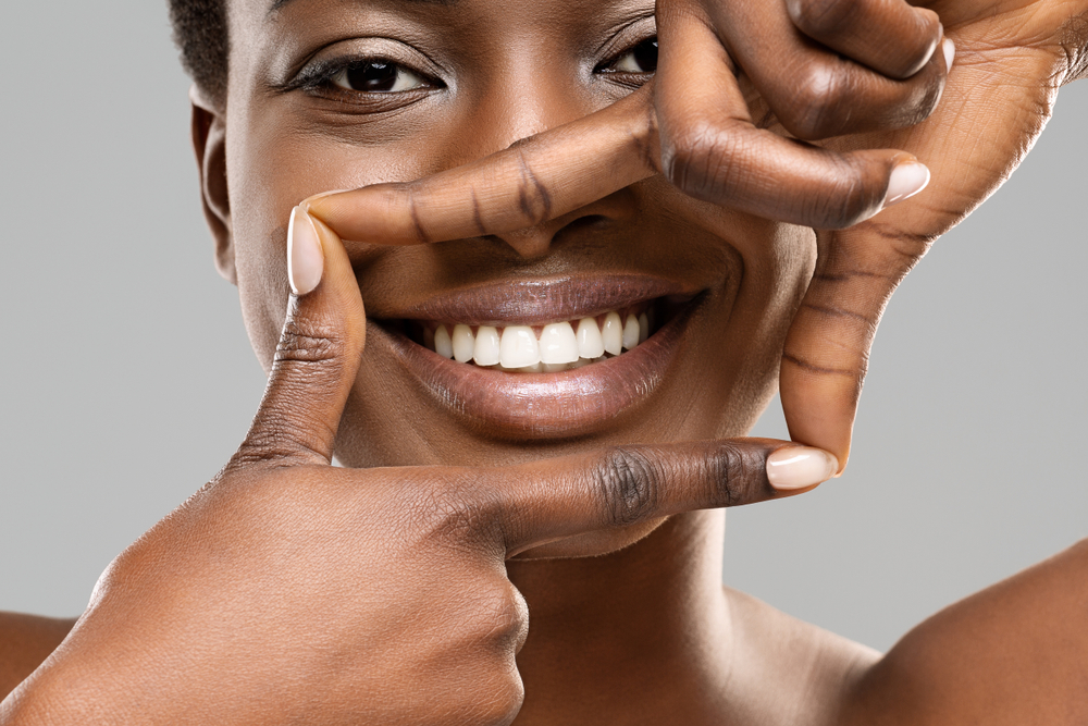 woman with white teeth framing her mouth with her hands